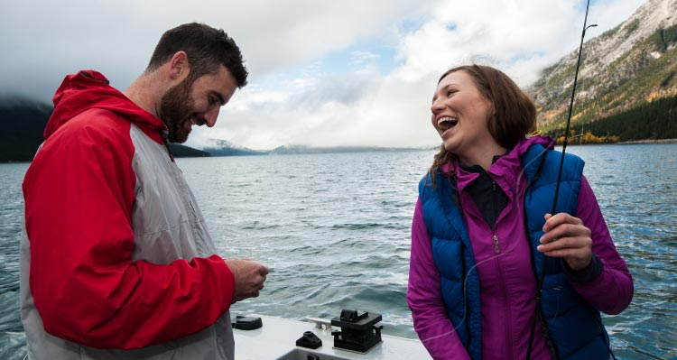 Two people get fishing rods ready on a boat.