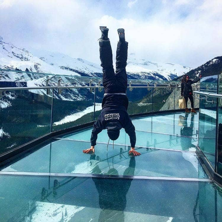 A person does a handstand on a glass walkway, overlooking a wide, snowy valley.