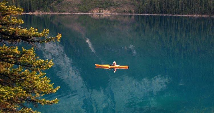 A kayaker paddles on a calm blue lake.