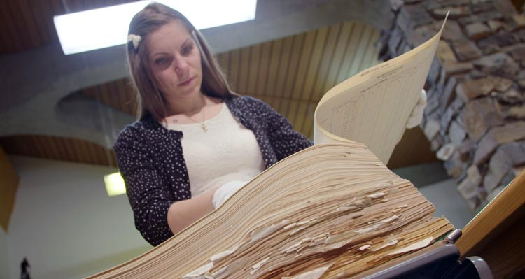 A researcher looks through historic documents from the Mount Royal Hotel.