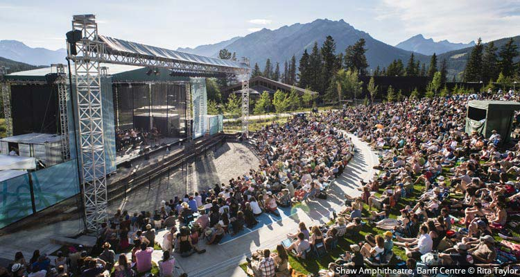 A large crowd in an outdoor amphitheatre watches a music performance with mountains and forests all around.