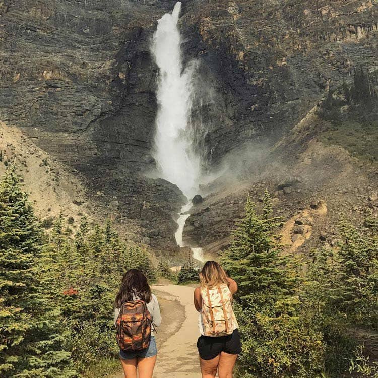 Two hikers stands at a misty waterfall by rocky cliffs.
