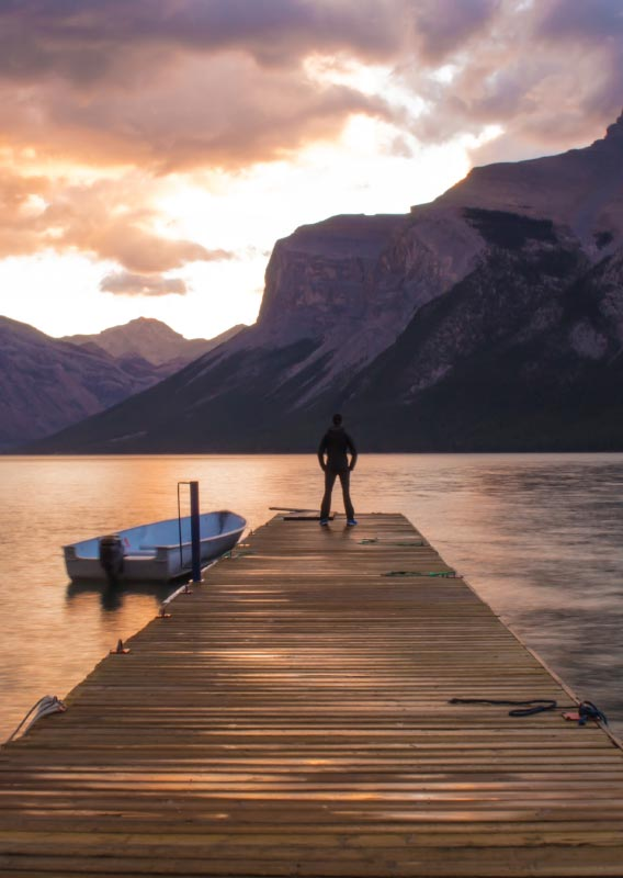 A person stands at the end of a dock overlooking a calm lake surrounded by mountains.