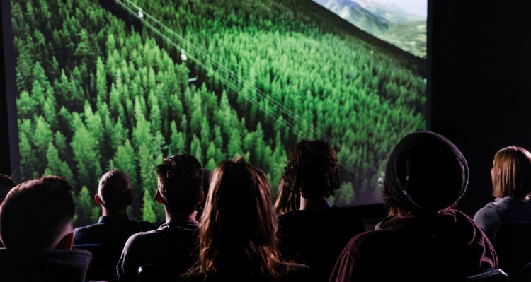 A group of people sit in a theatre watch a film showing the Banff Gondola on a green mountainside.