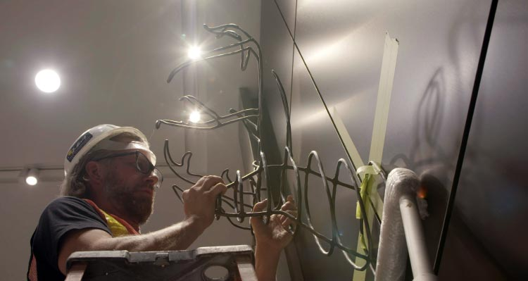 Jame Greisinger hangs his artwork, a steel-rod deer trophy on a wall.
