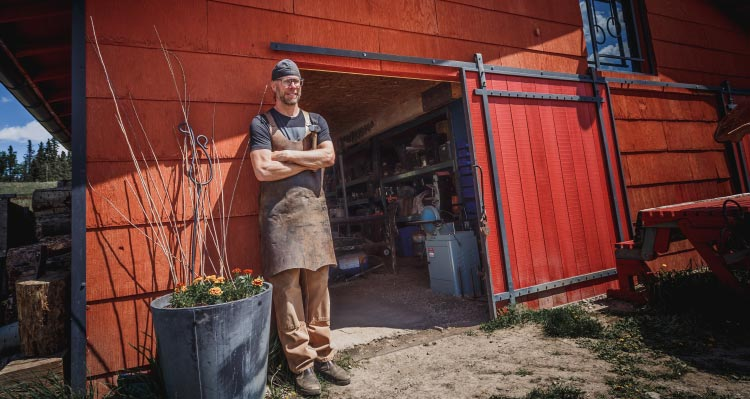 A blacksmith stands outside a red barn workshop.