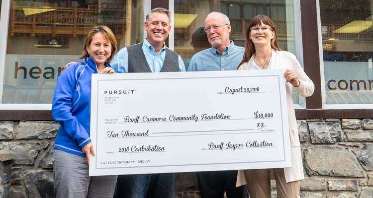 Four people hold a large cheque showing Pursuit's contribution to the Banff-Canmore Community Foundation