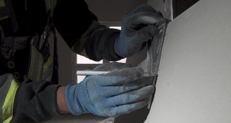 A worker wearing blue gloves cuts drywall