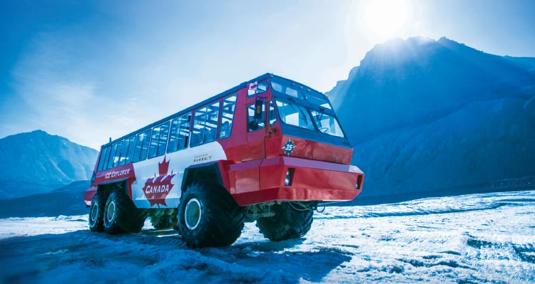 A red and white Ice Explorer vehicle drives on a glacier with sun glowing behind a mountain.
