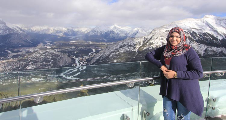 A woman leans against the railing at the Banff Gondola summit, overlooking Banff.