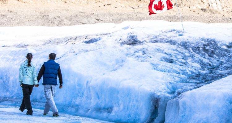 Two people walk along a glacier.