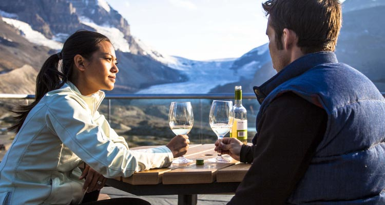 Two people enjoy a bottle of wine at a table overlooking a glacier.