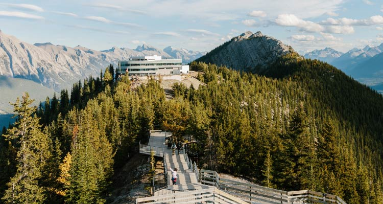 The Banff Gondola Upper Terminal atop a forested mountain-ridge with a boardwalk stretching forward.
