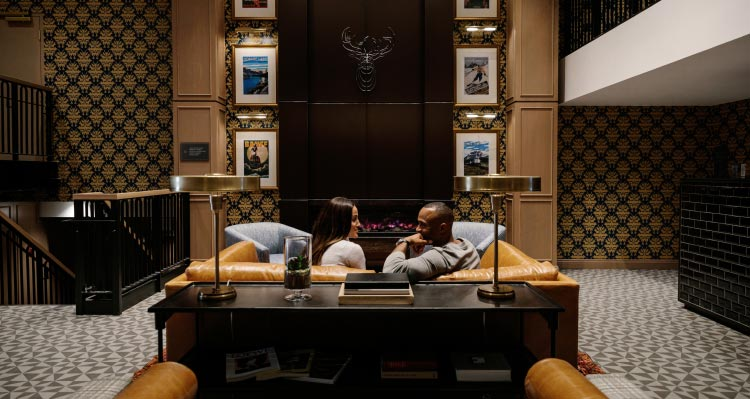Two people sit in a leather couch in a tall lobby with artwork above a fireplace.