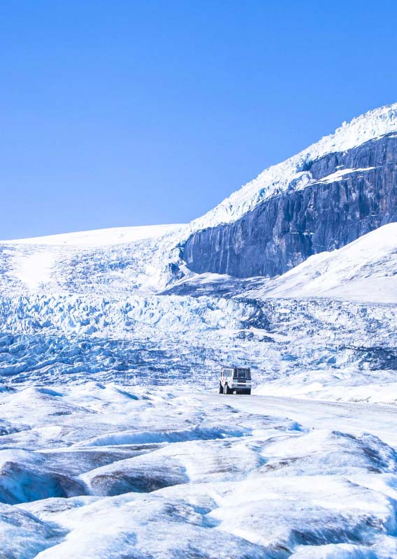 An Ice Explorer drives along the Athabasca Glacier towards the Columbia Icefield
