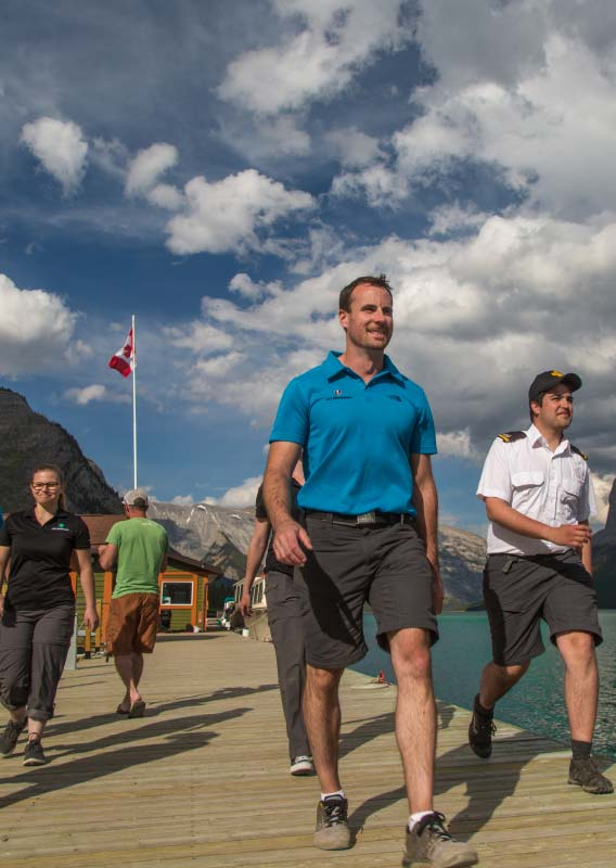 A group of Lake Minnewanka Cruise crew members walk down a wooden dock.