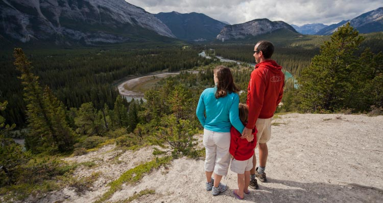 A family stands atop a rocky outcropping over a wide valley.