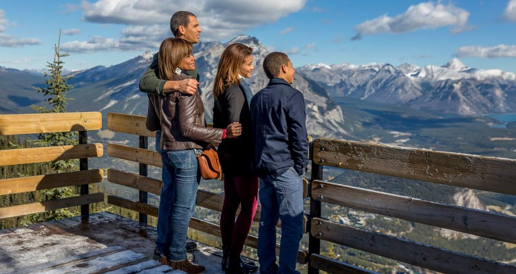 A family stands at an lookout point above mountains.