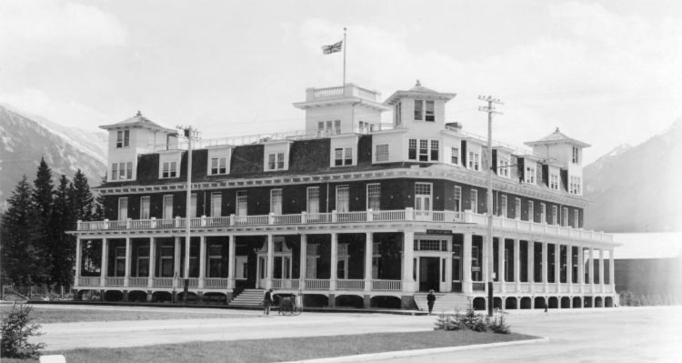 A black and white photo of a historic hotel with wraparound balconies.