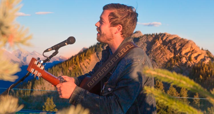 A musician sings and plays guitar atop a mountaintop.