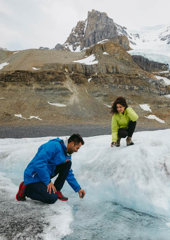 Two people crouch on a glacier, looking at and touching flowing glacial water.