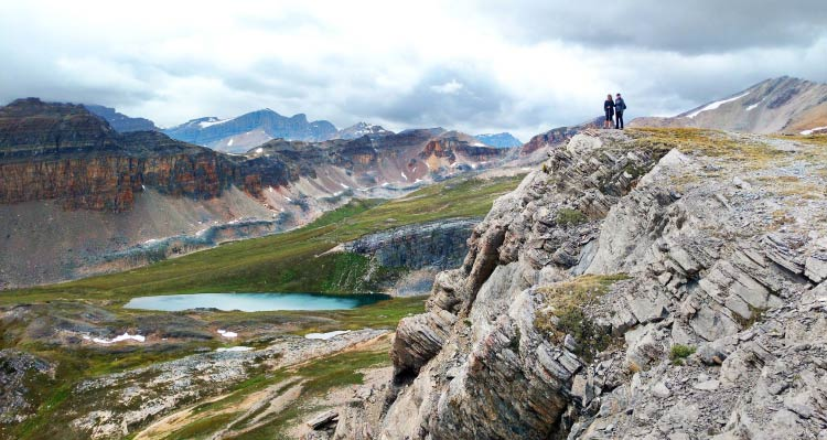 Two people stand atop a high cliffside above a green alpine meadow and small blue lake