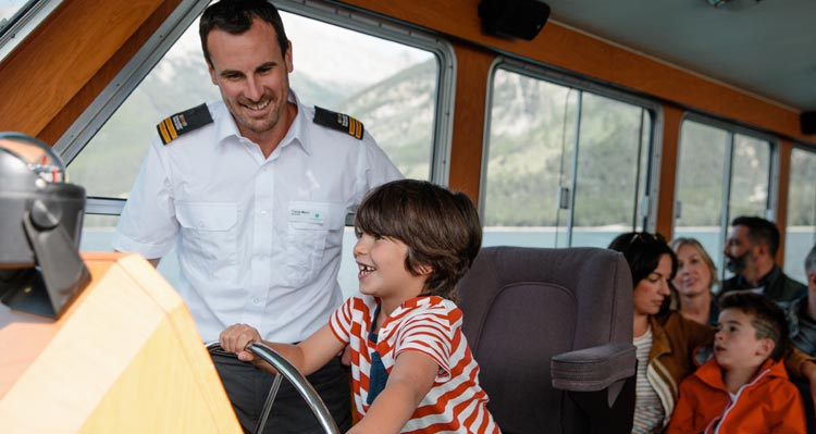 A child sits in the captain's chair of a boat with the boat captain.