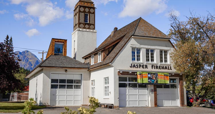 A historic firehall with a tower and garages with a half-hip roof.