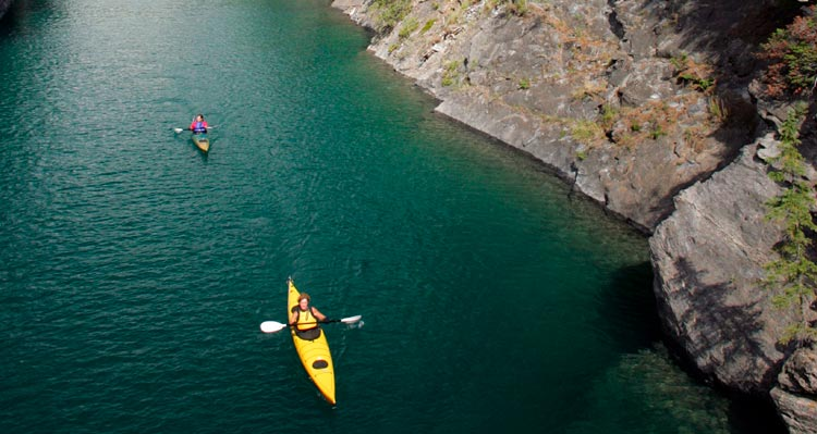 Two kayakers paddle down a river between steep rock walls.