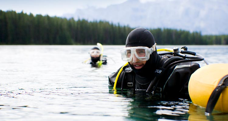 Two SCUBA divers prepare to dive on a lake surrounded by forests and mountains.