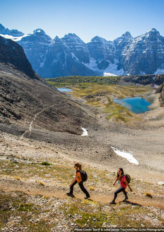 Two hikers walk along a trail above a blue lake and wide valley
