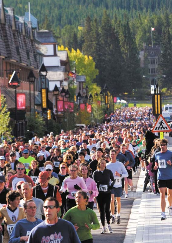 A crowd of runners race down a town street with forests behind.