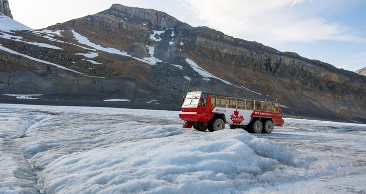 A red and white Ice Explorer bus sits on a field of ice with a mountain rising behind.