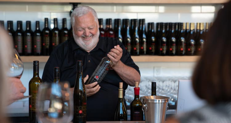 A bearded man smiles holding a bottle of wine at a wine bar.