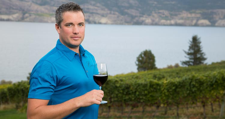 A man in a blue shirt holds a glass of wine in front of a lake.