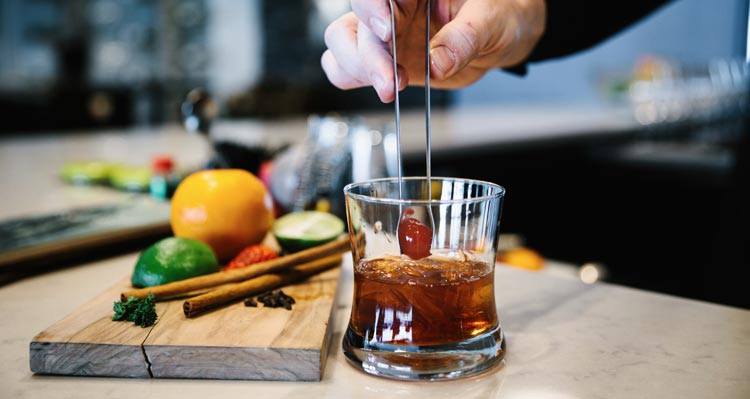 A bartender puts the finishing touches on a whisky cocktail