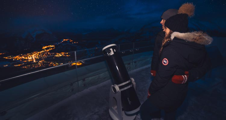 Two people stargaze high above a lit town.