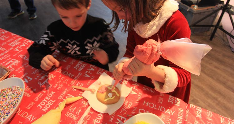 Two children decorate a cookie with icing