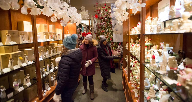 People walk through a shop of Christmas decorations.