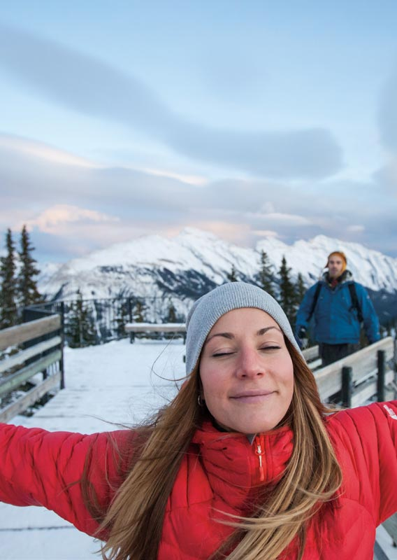A woman spreads her arms wide on the Sulphur Mountain boardwalk