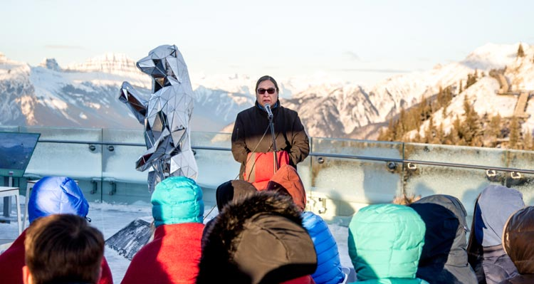 Barry Wesley addresses a group of students on a mountain observation deck.