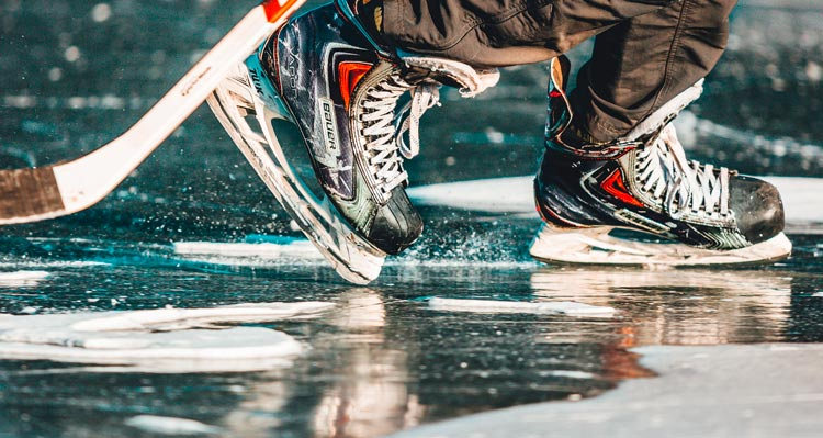 A close view of hockey skates and stick across a frozen lake.