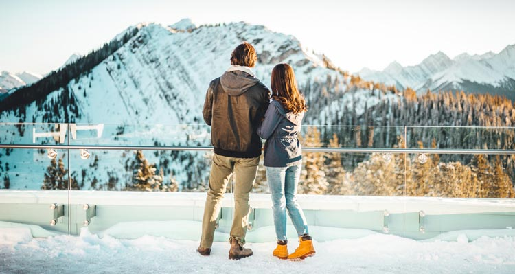 Two people stand at a viewpoint looking towards a mountain vista.