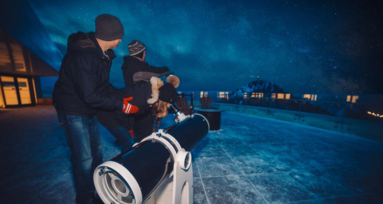 Two people look through a telescope.