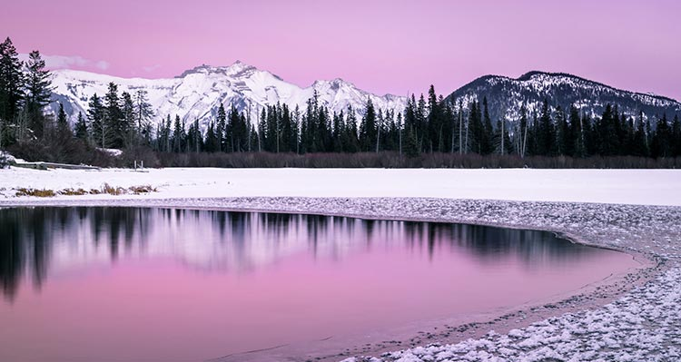 Pink sky over snow-covered mountains.