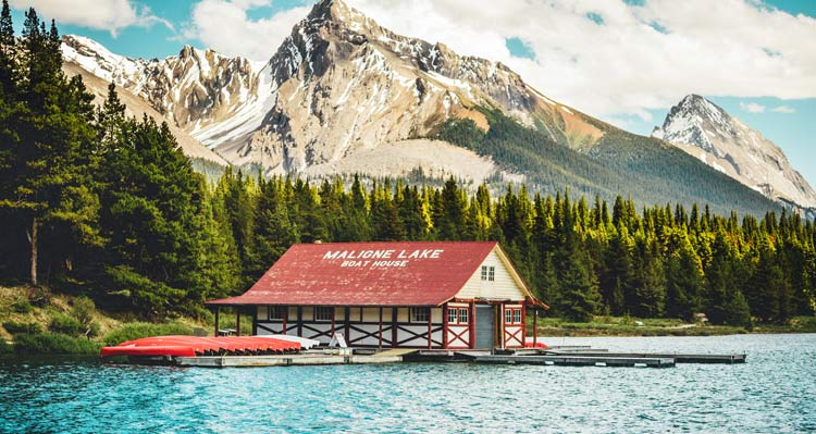 The Maligne Lake Boat House below forested mountain sides.