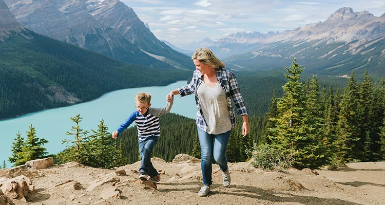 A mom and child walk on a path high above a blue lake.