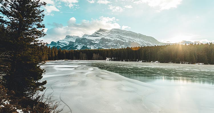 A view of mountains behind a frozen lake and forest