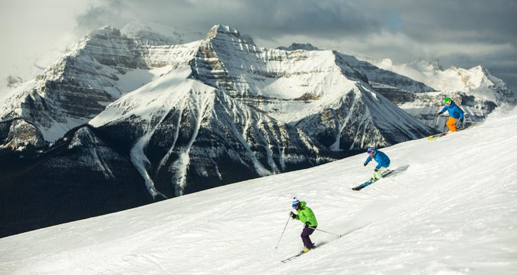 Three skiers on a snowy mountainside.