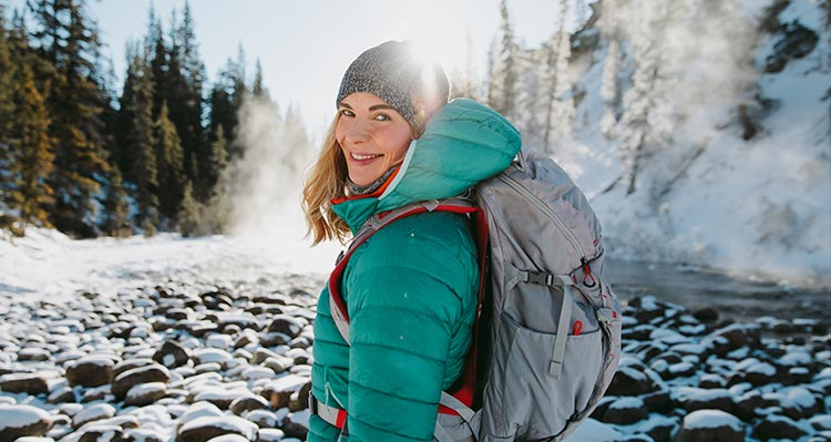 A woman wears a teal jacket in a wintry canyon.